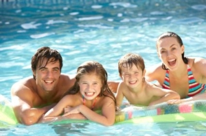 American Family Vacation - Young Family in Swimming Pool