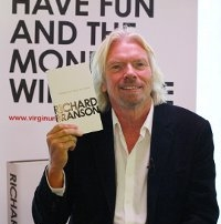 Richard Branson Holding a Copy of Screw Business as Usual