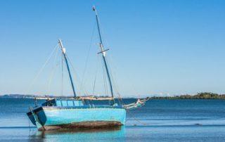 A rising tide is lifting a blue sailboat
