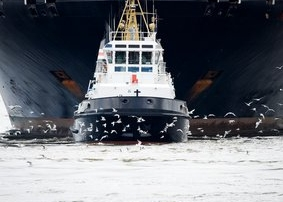 A Small Tugboat Pushes a Large Freighter