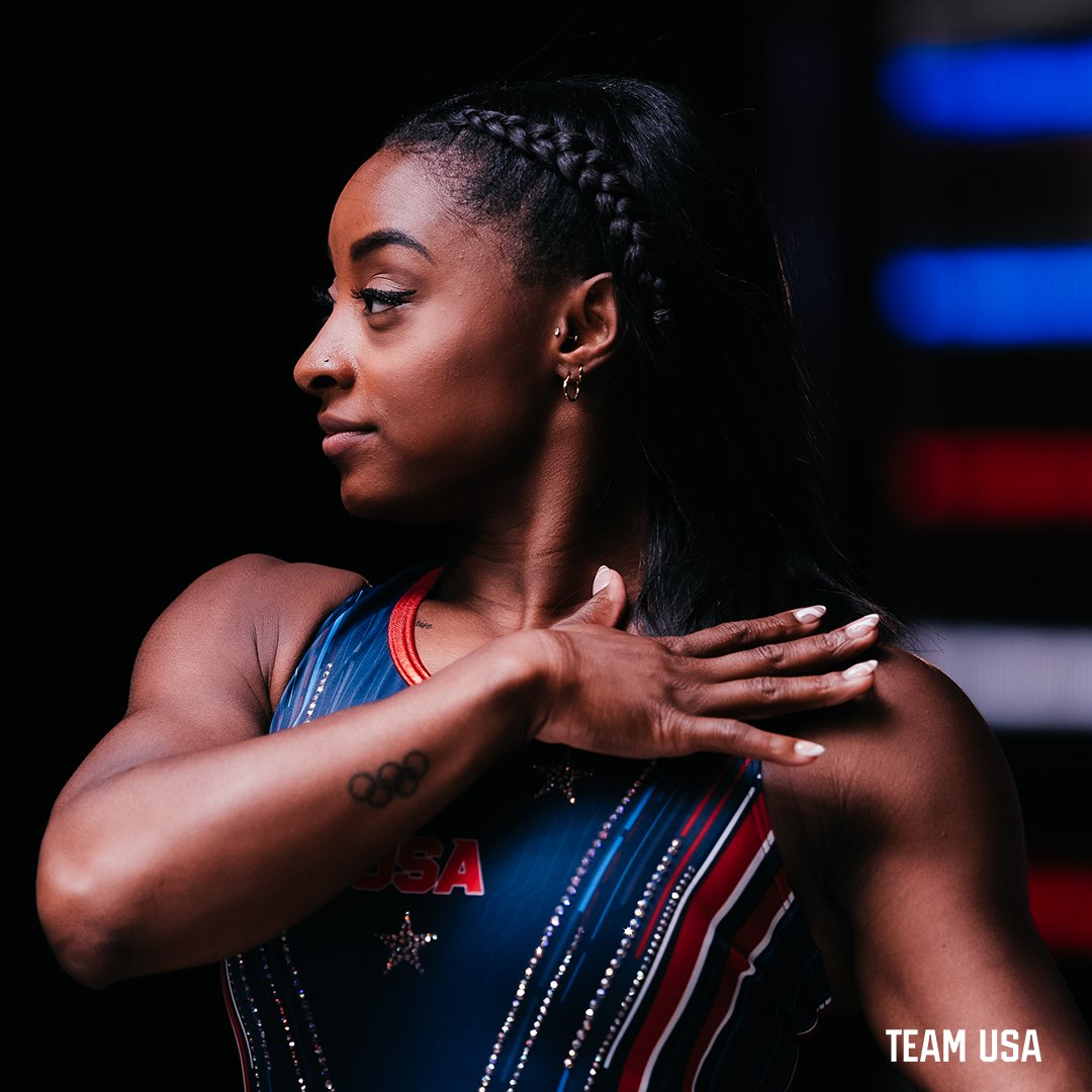 Simone Biles Photo from Team USA - Hand crossed over shoulder, looking to her right, Olympic Rings Tatoo on arm