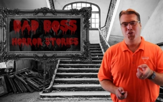 """Author Ben Lichtenwalner Stands in an Abandoned Mental Hospital, Gesturing at the Viewer, with a Sign Reading """"Bad Bosses Horror Stories"""" in Red Lettering"""